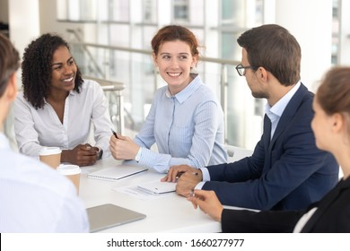 Young happy smiling woman talking to colleague in office. Fun team conversation, leader, coach woman briefing and discussing work issues with white man, businessman and businesswoman relationship.