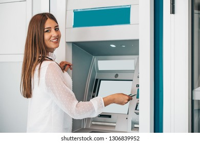 Young happy smiling woman withdrawing money from credit card at ATM - Image