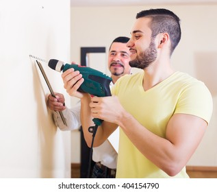 Young happy son and elderly father drilling wall indoors