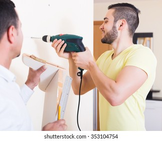 Young happy son and father drilling wall indoors