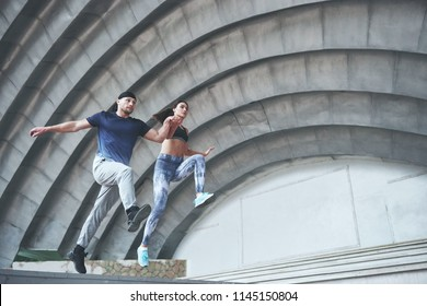 Young happy sports couple in the city street, performing parkour