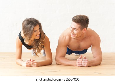 Young happy sportsmen couple woman and man making plank