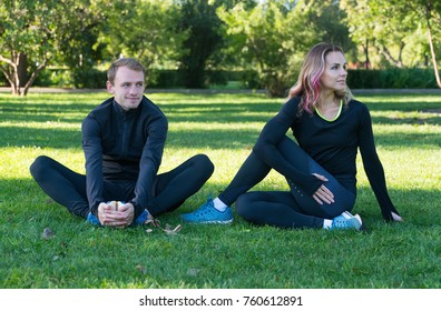 Young happy sporty couple sitting on a meadow in a park laugh after training, sunny day