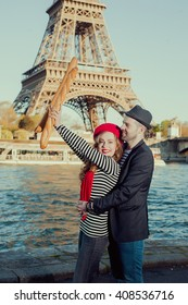 Young happy stereotypical french couple having fun with baguettes under the Eiffel Tower in Paris, France