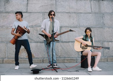 Young and happy street musicians band with guitars and djembe in city