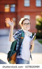 Young happy student with books and notes showing greeting gesture. Smart young girl in University campus. Learning and education for young people.