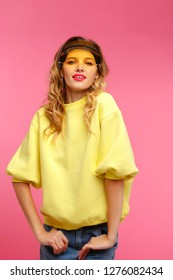 Young happy student girl in studio pink background. Wearing yellow sweatshirt and sunshied