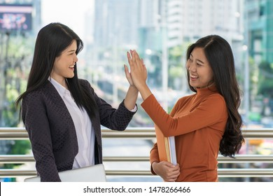Young happy student holding books and slap hands or hi five together at campus.
