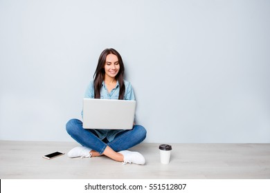 Young happy student sitting on floor and typing on laptop