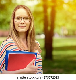 Young happy student woman with the book in her hands is standing and smiling in the university park