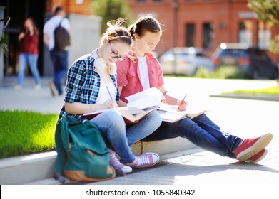 Young happy students with books and notes outdoors. Smart young guy and girl in University campus. Learning and education for young people.