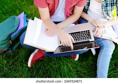 Young happy students with laptop, books and notes outdoors. Smart young guy and girl doing their homework in University campus. Learning and education for young people.