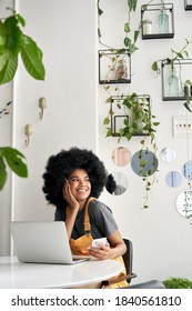 Young happy stylish African American gen z hipster teenage girl student with Afro hair laughing, looking through window, sitting at table in modern cozy cafe interior, holding phone, using laptop.