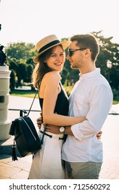 Young happy stylish couple in city centre on sunset or sunrise