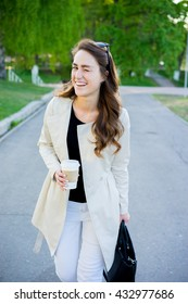 Young happy successful business woman walking in the city street and drink coffee