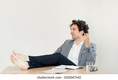 Young, happy, successful Caucasian businessman sitting in the office with barefoot on desk and relaxing.