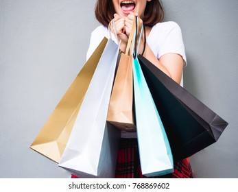 Young happy summer shopping asian woman with shopping bags on grey background at copy space. Beautiful young mixed race asian woman. Chinese asian woman shopper smiling happy.