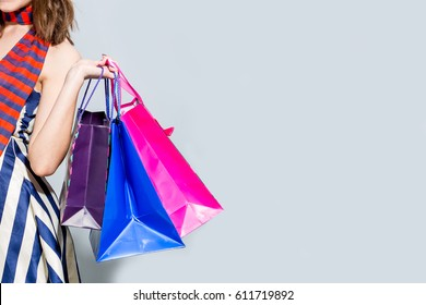 Young happy summer shopping woman with shopping bags isolated on grey background