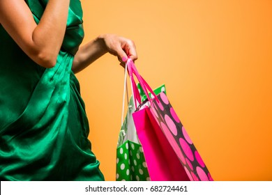 Young happy summer shopping woman with shopping bags isolated over bright orange background, detail, focus on hand with bags
