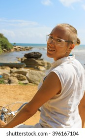 Young happy suntanned woman riding bicycle across river bridge next to tropical park and enjoying beautiful seascape on sunny summer day, view 1