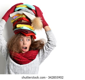 Young happy surprised girl with many warm winter hats in different colors with text copy space looking at the corner on white background