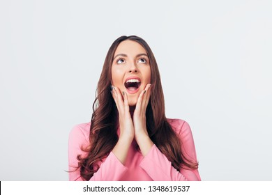 Young happy and surprised woman looking up and holds cheeks by hands isolated on white backround. Wow face concept