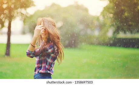 Young happy teen girl with long wavy hair walking under summer rain. Positive funny woman enjoying a spring shower raindrops spray on a rainy day outdoors. Spring season, bad weather and rain concept.