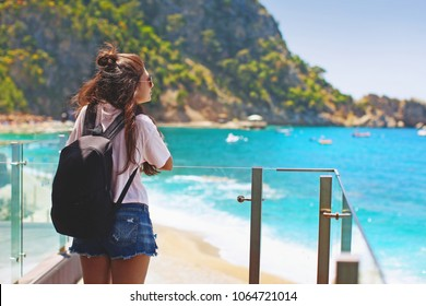 Young happy teenage girl with hipster with backpack stands with back and looks at beach and mountain landscape resting in Oludeniz, Fethiye district in Turkey