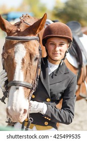 Young happy teenage rider girl with horse. Sportswoman equestrian portrait