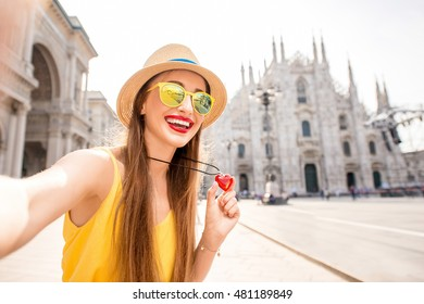Young and happy tourist making selfie photo in front of the famous Duomo cathedral in Milan. Happy vacations in Milan