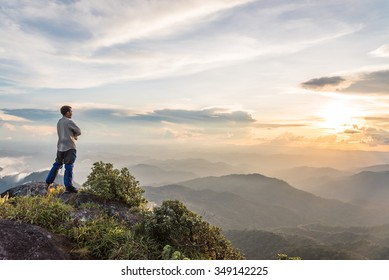 Young happy tourist on top of a mountain enjoying valley view
