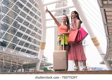 Young happy tourists female with suitcase and shopping bags,city background - shopping and traveling concept.