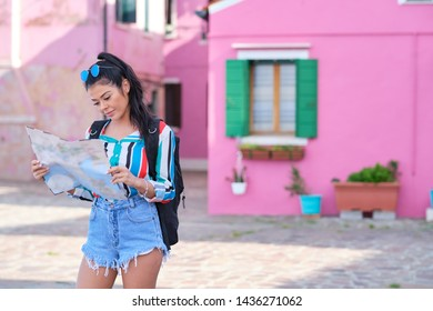 young happy traveler woman looking at the tourist map among colorful houses on Burano island, Venice. Tourism in Italy concept