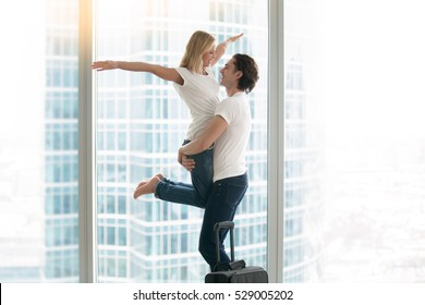 Young happy traveller couple laughing, embracing, having fun, feeling euphoria, family moved into a bigger flat, inherit a property, rented cool apartment on trip wedding gift, travelling in honeymoon