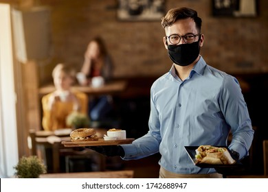 Young happy waiter wearing protective face mask while serving food in a restaurant.