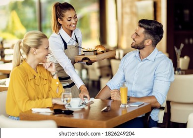 Young happy waitress serving a meal to her guest in a restaurant.
