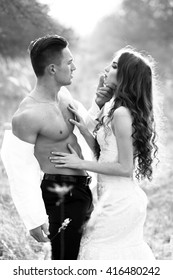 Young happy wedding couple of pretty woman and man undressing in field outdoor, black and white