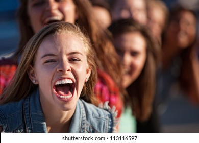 Young happy white teenage girl shouting with friends