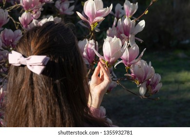 A young happy womam is walking in the spring flowers white