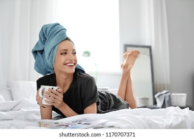 Young happy woman with aromatic coffee lying on bed at home. Lazy morning