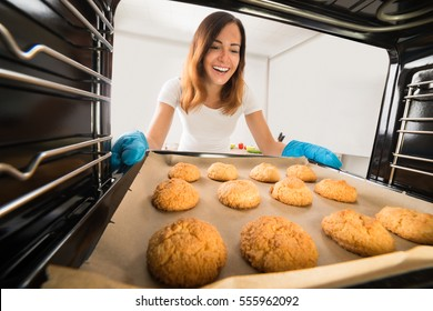 Young Happy Woman Baking Fresh Cookies In Oven At Kitchen