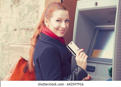 Young happy woman with bank card using ATM