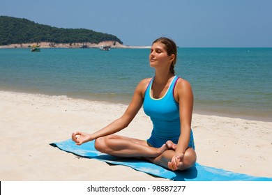 Young happy woman in the beach making yoga