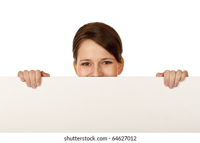 Young happy woman behind blank advertisement board. Isolated on white background.