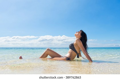 Young happy woman in black bikini enjoys sunny day on beach. Tropical vacation