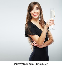 Young happy woman in black dress with glass. Beautiful model portrait isolated over studio background