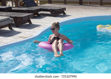 Young happy woman in black swimsuit, pretty lady in pool swimming with Inflatable Circle