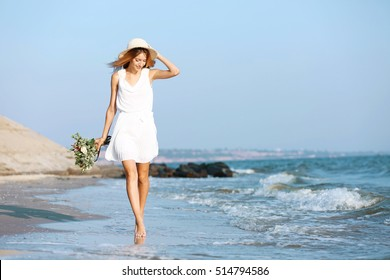 Young happy woman with bouquet of flowers walking along seashore