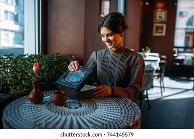 Young happy woman in cafe with casket and jewelry