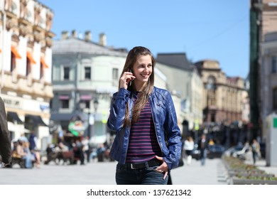 Young happy woman calling by phone on the street